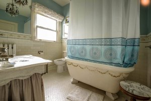 Bath and shower next to toilet and sink in bathroom