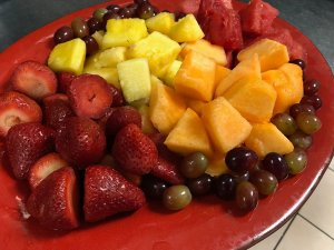 Strawberries, pineapple, mango, and grapes on a tray