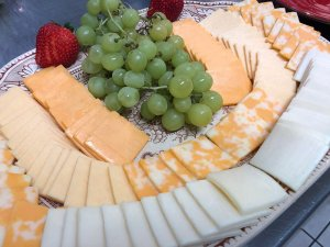 Bunch of grapes and rows of assorted cheese slices on tray