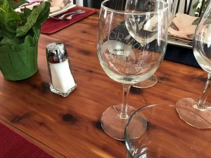 Glasses next to salt shaker and flowerpot on dining table