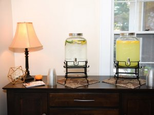 Drink dispensers and lamp on table next to window