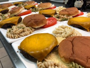 Cheeseburgers and pasta on rows of plates