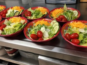 Bowls of lettuce and toppings on kitchen countertop