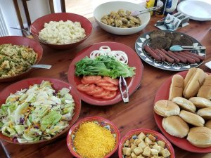 Burger toppings and sides laid out on table