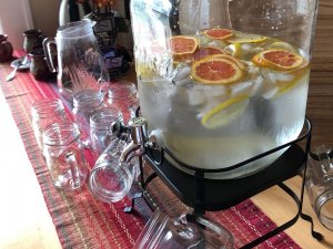Water dispenser at table with glass mugs