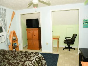 Cabinet, television, and desk chair in small seperate rooms across from bed