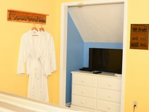 Bathrobe hung on coat rack next to television