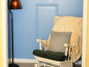 Rocking chair and pillow next to standing lamp