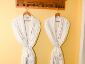 Bathrobes hung on decorated wood coat rack