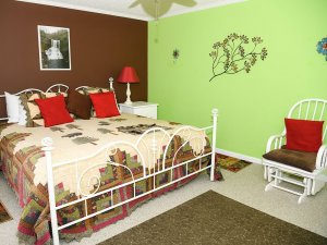 Metal-framed bed next to wall decoration and rocking chair