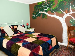 Queen bed in seperate room with decorated wall