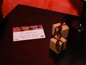 Small boxes of chocolates and card on bedside table