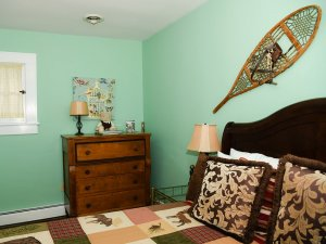 Dresser with lamp, books, and teddy bear next to bed