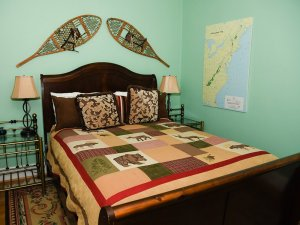 Queen-sized bed next to map of appalachian trail canvas