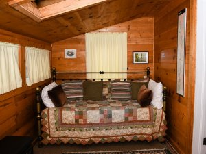 Pillows lining day bed in wooded room with slanted ceiling