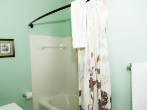 Curtain hanging from rod of shower in bathroom