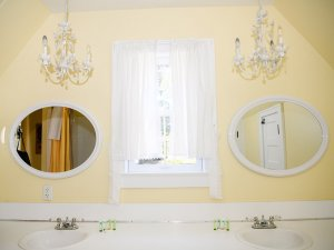 Round mirros and window above sinks in bathroom