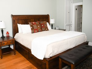 King-sized bed next to endtable and bench