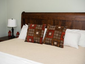 Decorative pillows against headboard of wood-framed bed