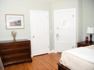 Wooden dresser with 3 drawers next to doors of room