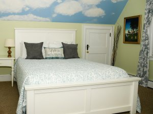 Pillows on queen-sized bed next to short door