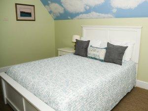 Queen bed under vaulted ceiling in bedroom