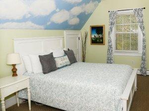 Window and portrait next to bed and door