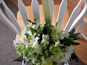 Floral arrangement hung from back of wood chair