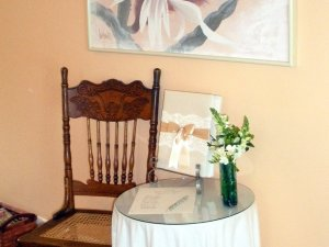 Wood chair set next to small table with gift and flowers on it