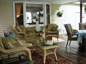 Outdoor cushioned patio furniture around table under a porch roof
