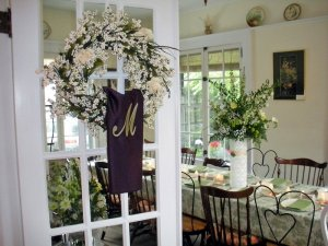 Floral wreath on glass door to dining room with set dining table