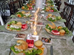 Candle-lit table set with plates of croissant sandwiches and salad