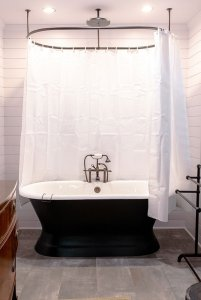 Bathtub and curtain rod in middle of bathroom