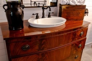 Wood sink countertop with vase, chest, and towels