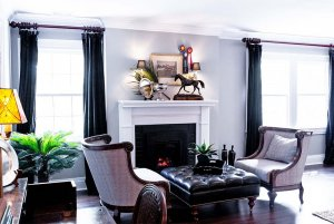 Cushioned chairs and ottoman infront of fireplace and windows