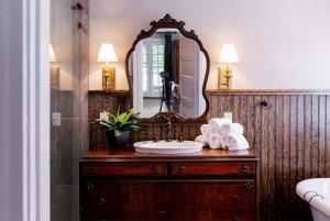 Wood countertop and sink under mirror in bathroom