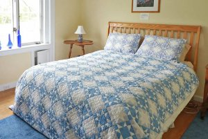 Quilted bedding on a wood framed bed