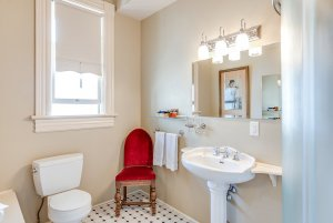Toilet, chair, sink, and mirror in bathroom