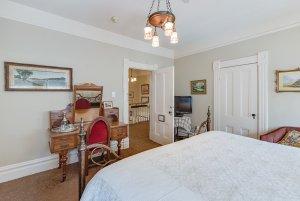 Vanity next to doorway to bedroom with television