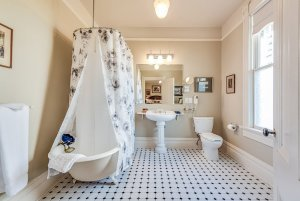 Shower with wrap-around shower curtains in bathroom