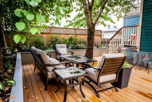 Chairs around table next to tree on wood deck outside