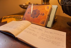 Open guests check-in book with signatures on table