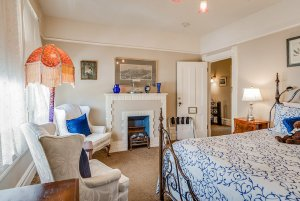 Fireplace, chairs, lamp, and bed in bedroom