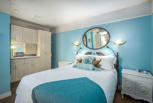 Kitchenette and queen-sized bed in bedroom