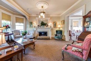 Fireplace in living room with cushioned chairs and table