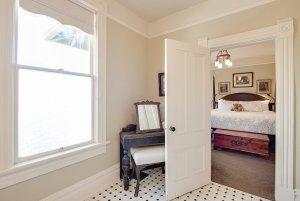 Vanity, bench, and window in bathroom next to bedroom