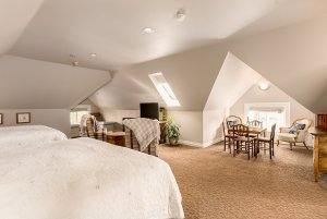 Vaulted ceilings above seating area, beds, and table with chairs