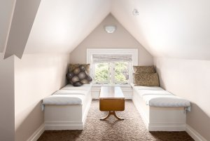 Cushioned benches and table next to window under vaulted ceiling