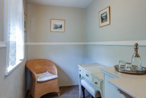 Wicker chair, window, and desk in smaller room