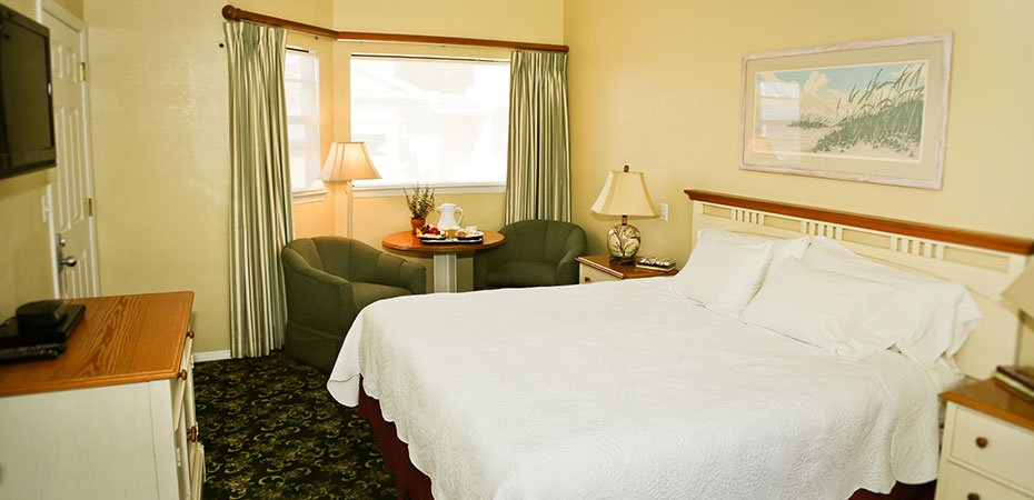 Cottage King Whirlpool Room with a bed, chairs, table, TV